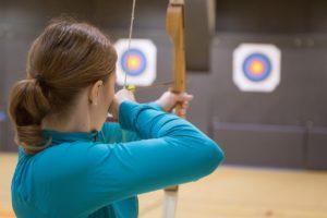 Femme de dos qui vise une cible avec un arc (tir à l'arcà