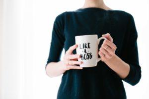 Femme avec une robe noire portant une tasse avec l'inscription 'like a boss'